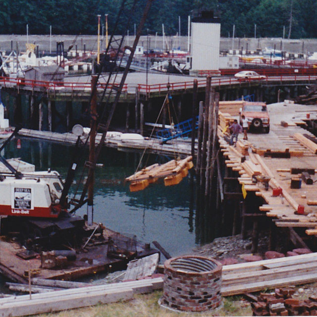 Stringers pilings now decking and a dock being lifted into the water